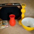 thrifting finds: vintage suitcase, vintage yellow metal lamp, orange vase, vintage patterns