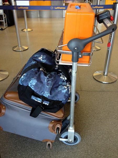 orange sewing machine in luggage cart at airport
