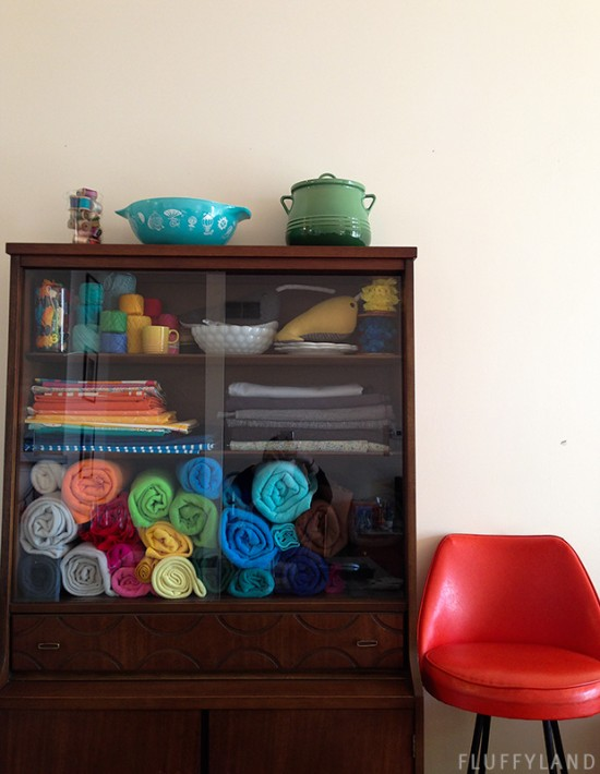 fabric storage: rolls of colorful fleece in my vintage hutch